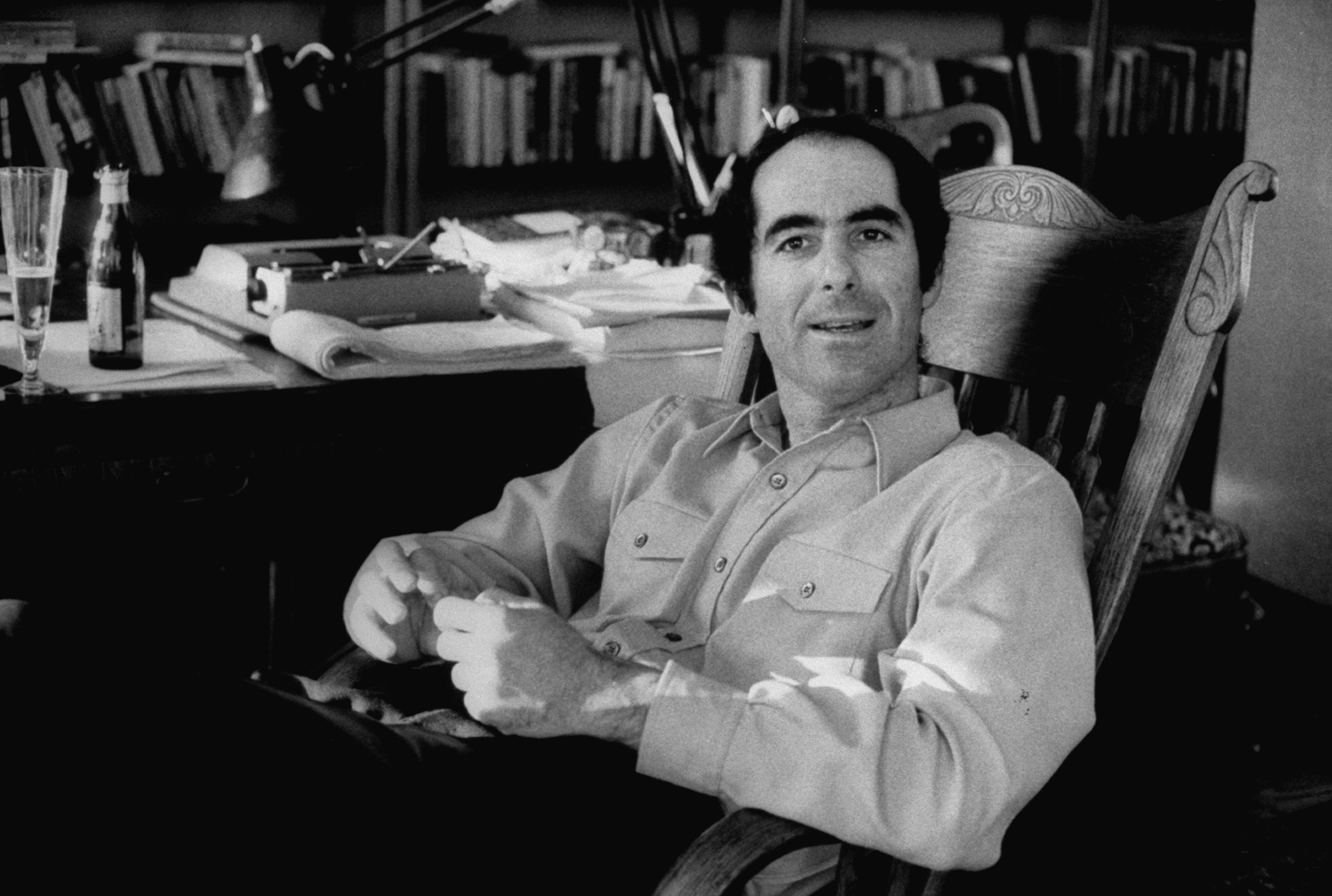 Pulitizer Prize- and National Book Award-winning novelist Philip Roth drinking a glass of beer as he pauses during work on a man